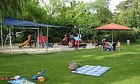 Bild vom Spielplatz mit Liegewiese im Vordergrund